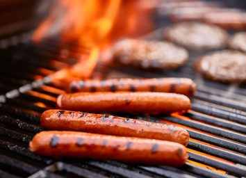 hot dogs burgers on flaming grill