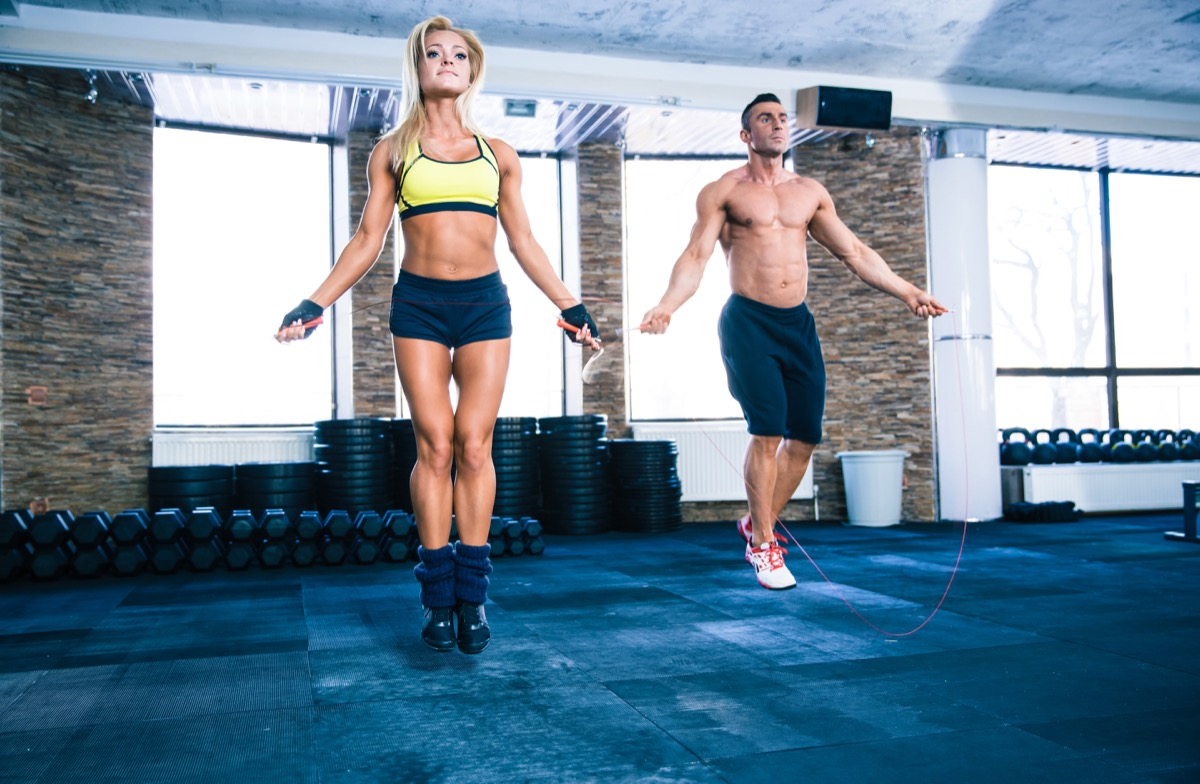 man and beautiful sporty woman workout with jumping rope in crossfit gym