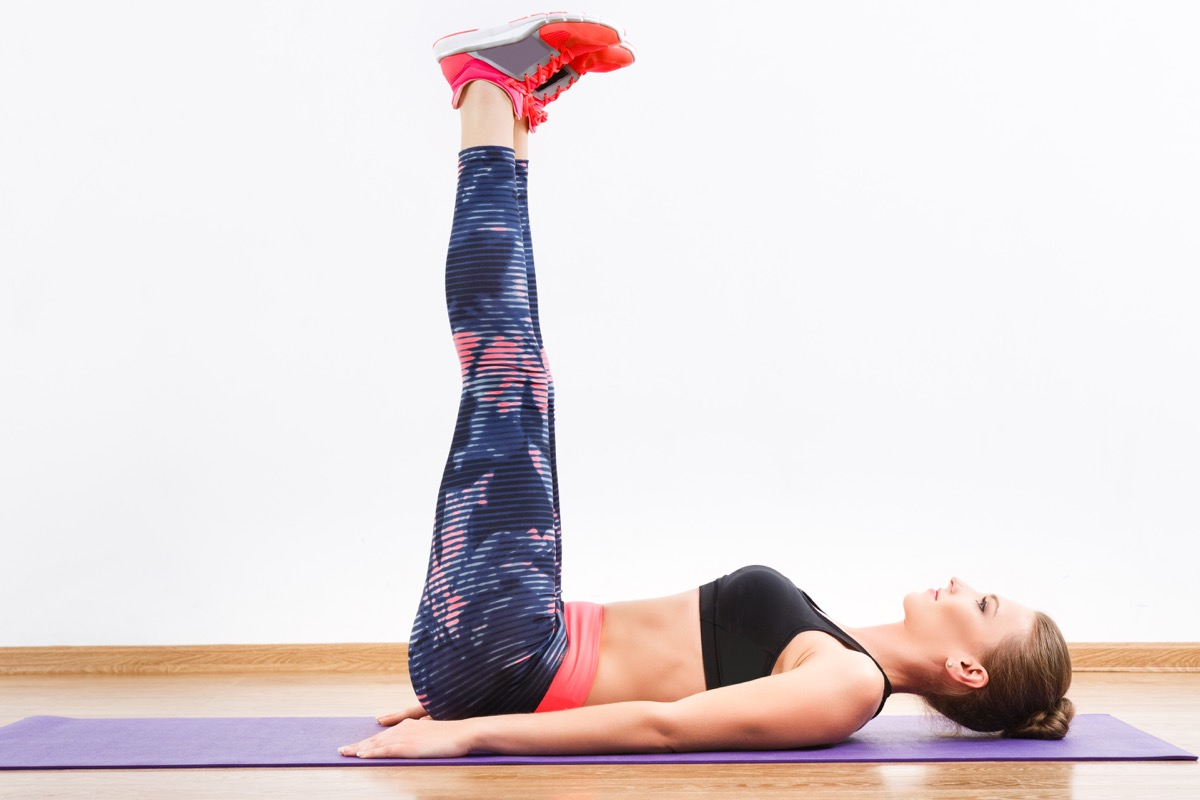 girl with dark hair wearing pink snickers, dark leggings and black short top doing leg raise at gym, fitness, white wall and wooden floor