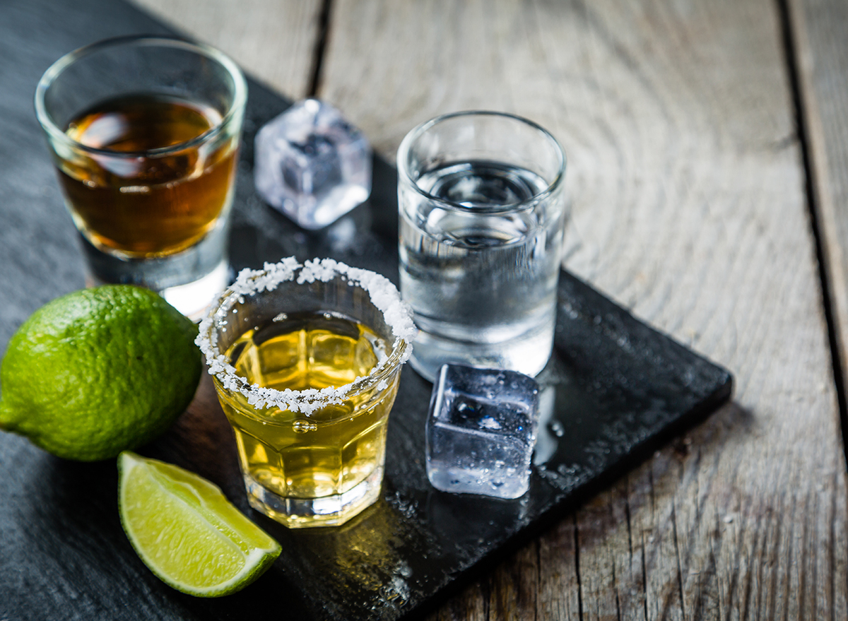 three shots of different liquors with ice cubes and lime