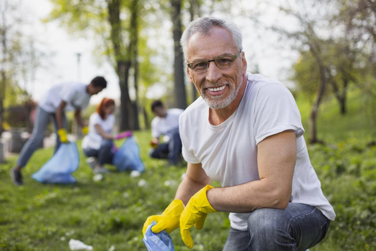 Work as volunteer. Experienced senior volunteer holding garbage bag