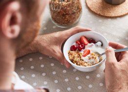 Man scooping into yogurt fruit granola breakfast bowl