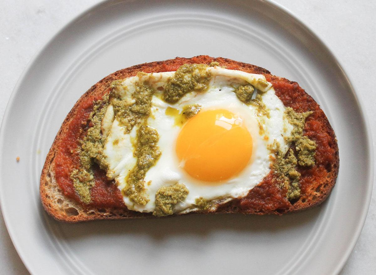 marinara pesto egg toast on grey plate and marble counter