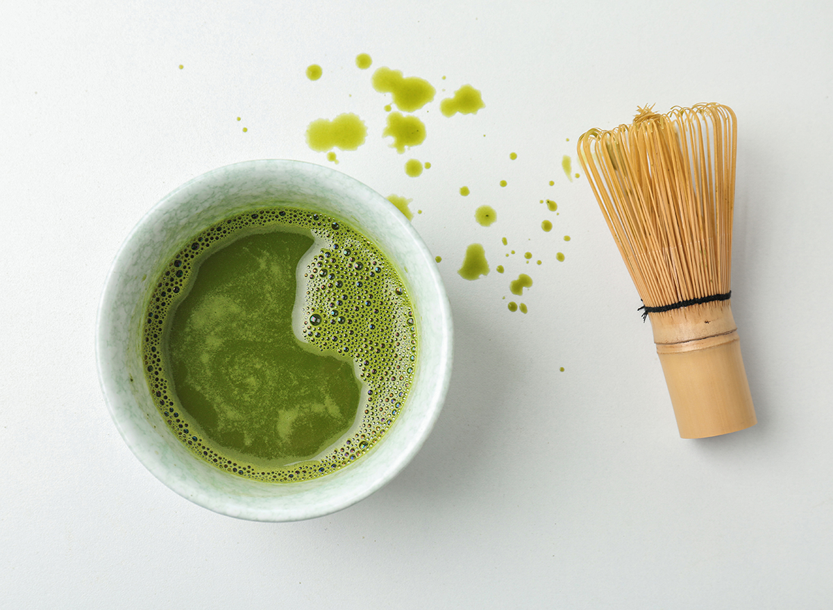 matcha green tea with whisk on white countertop