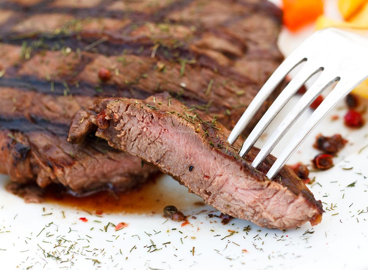 medium cooked steak fork white surface