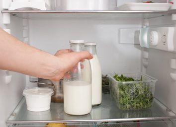 person putting a glass jar of milk in the refrigerator