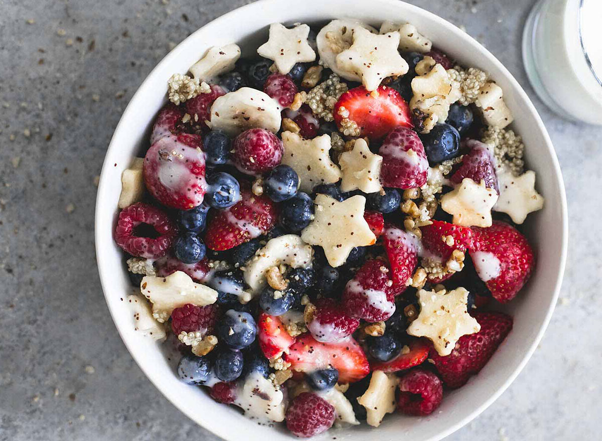 fruit salad with strawberries, blueberries, star shaped apple slices and quinoa in a white bowl on gray background