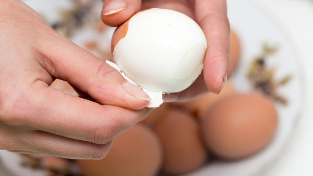 peeling hard boiled eggs with hands easily over a bowl of eggs to be peeled