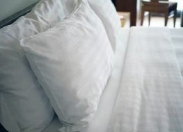Big white soft pillows on a white luxury cozy bed with clean white sheets.