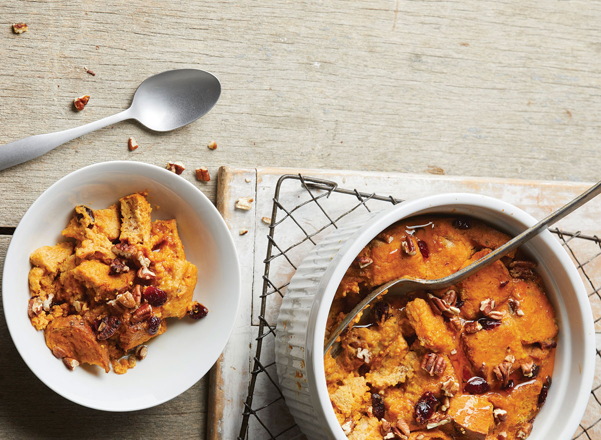two bowls of pumpkin bread pudding with spoons on wire rack and wooden background