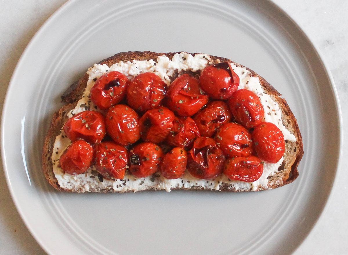 ricotta cheese roasted tomatoes basil balsamic toast on grey plate and marble counter