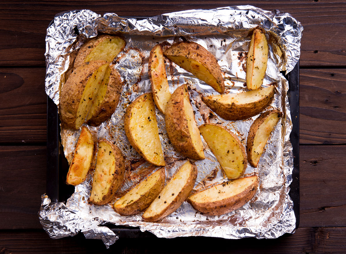 Roasted baked potato wedges on aluminum foil lined baking tray