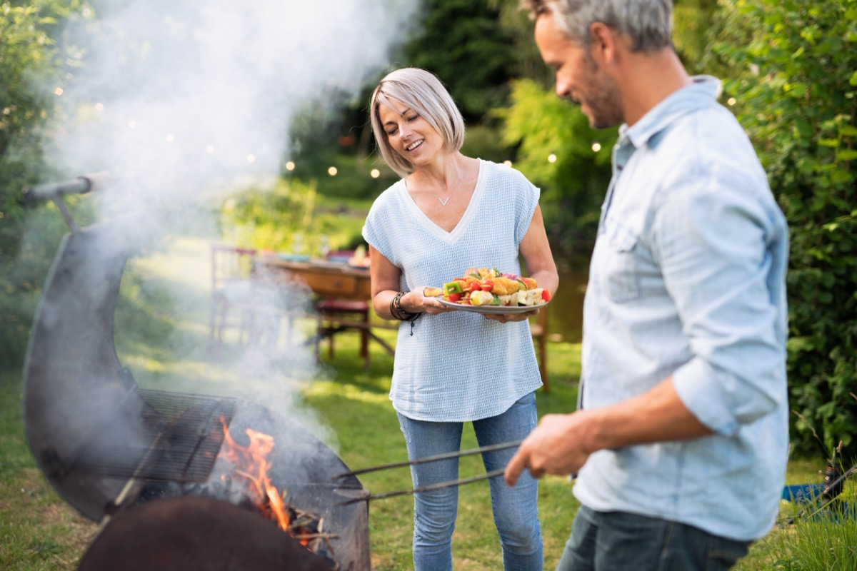 In summer. A nice couple prepares a bbq to welcome friends in the garden. She's holding a plate of grilled skewers