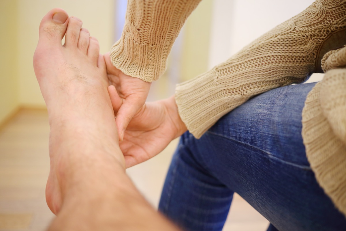 Woman massages leg of man in room, part of body, swelling right after sprained foot