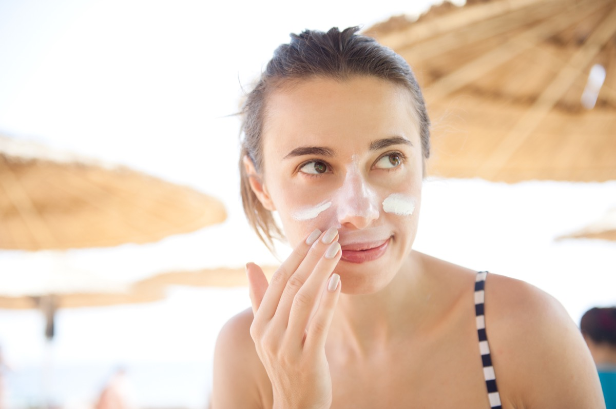 woman smears face sunscreen at the beach for protection