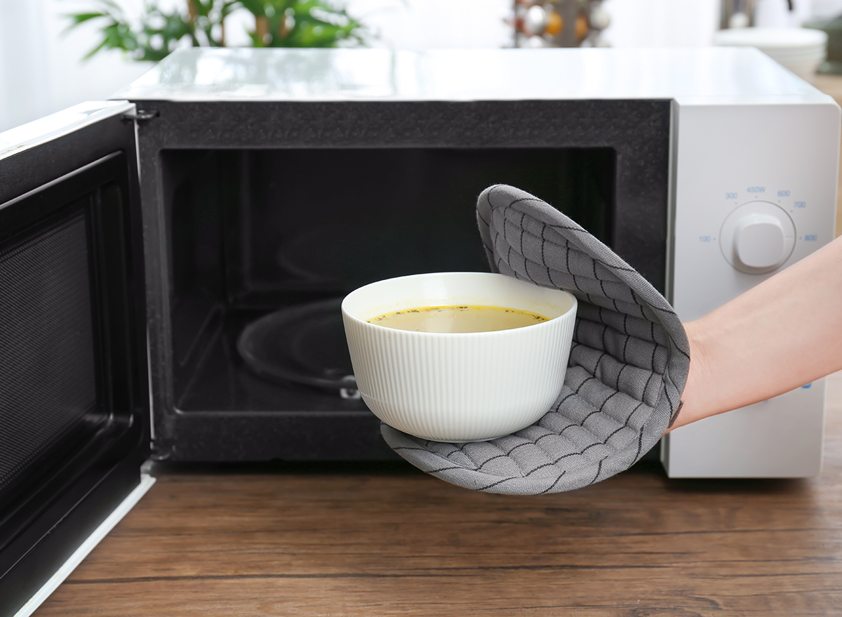 putting soup in microwave with hot pad