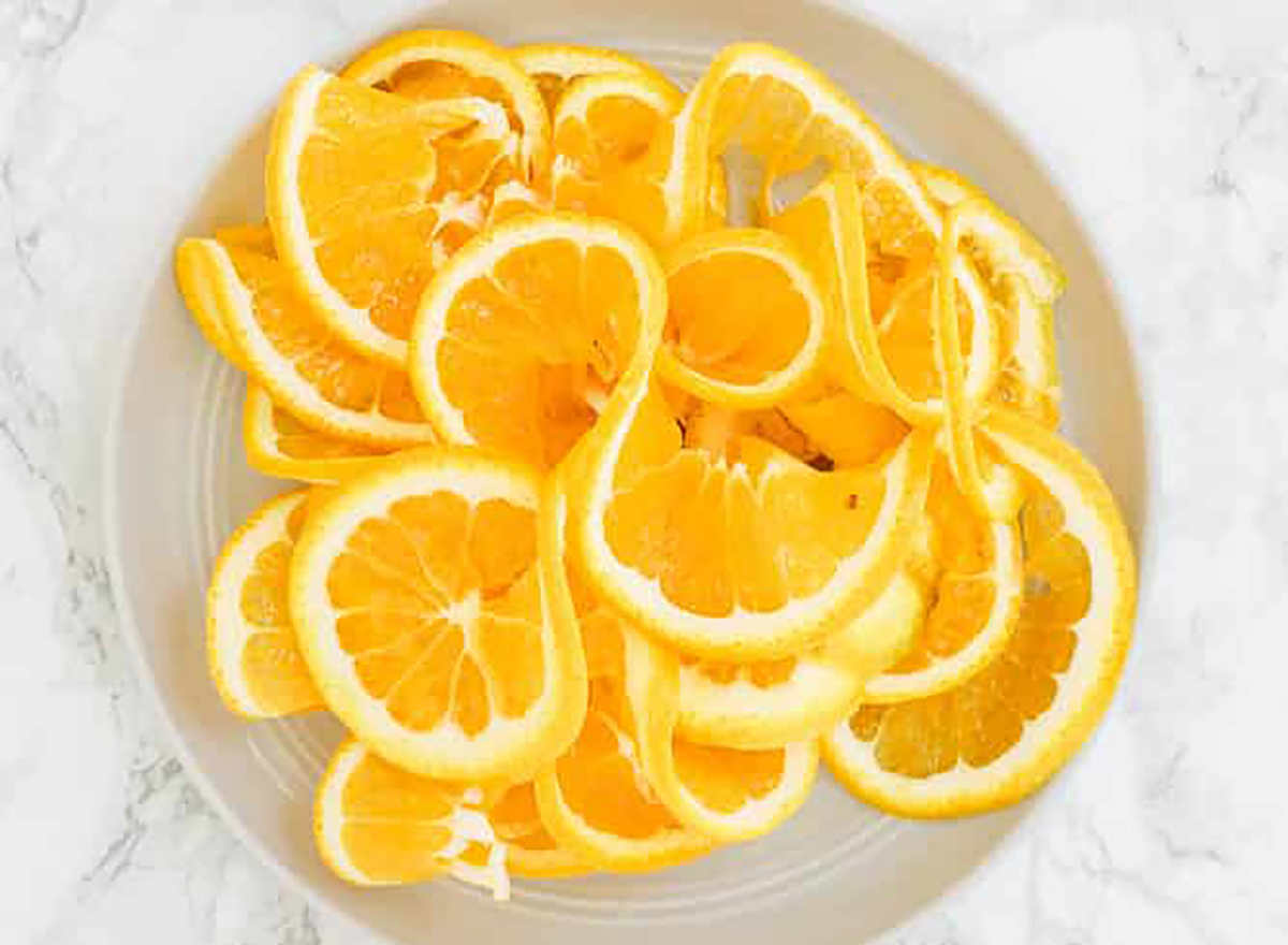 spiralized oranges on a grey plate on a marble counter top