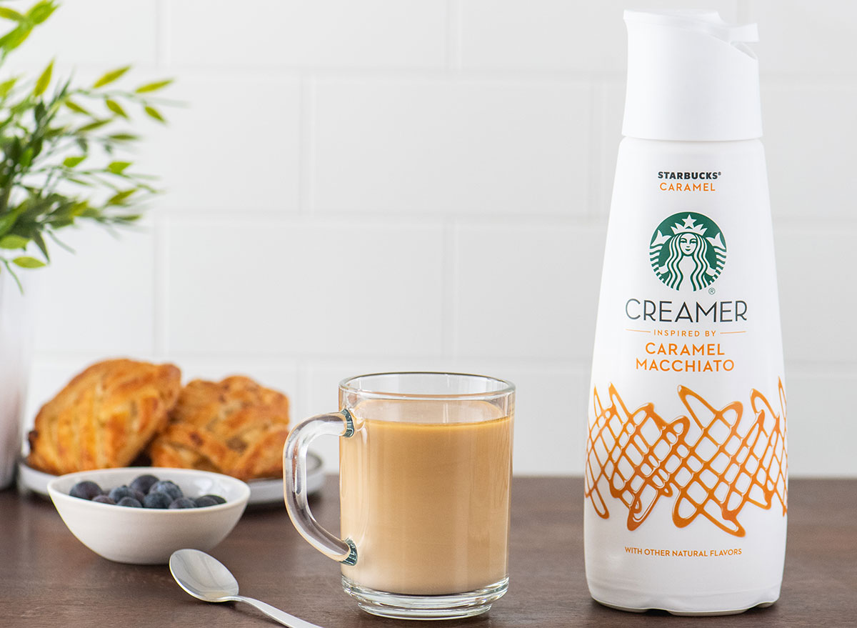 container of starbucks caramel macchiato coffee creamer with glass cup of coffee and scones on table