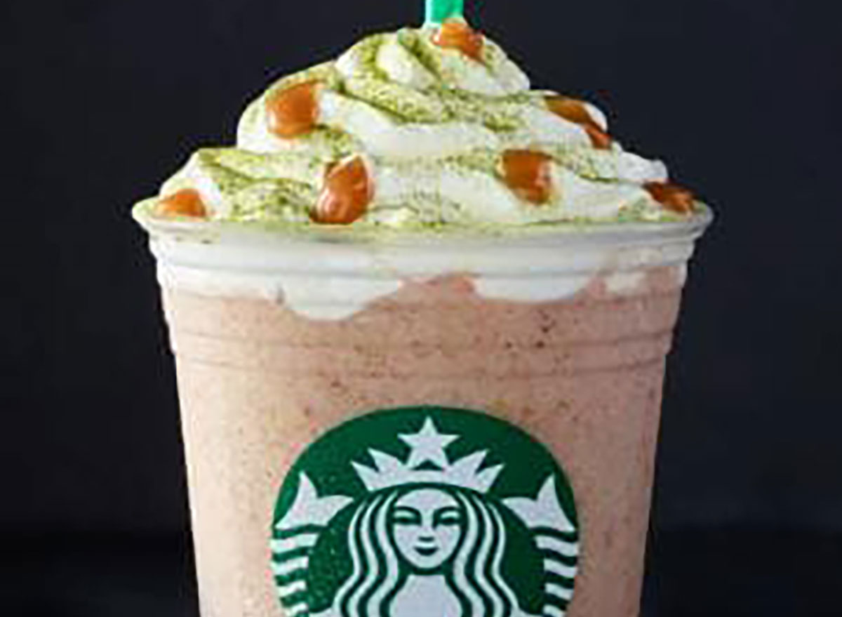 starbucks fruitcake frappucino in disposable plastic cup on black background