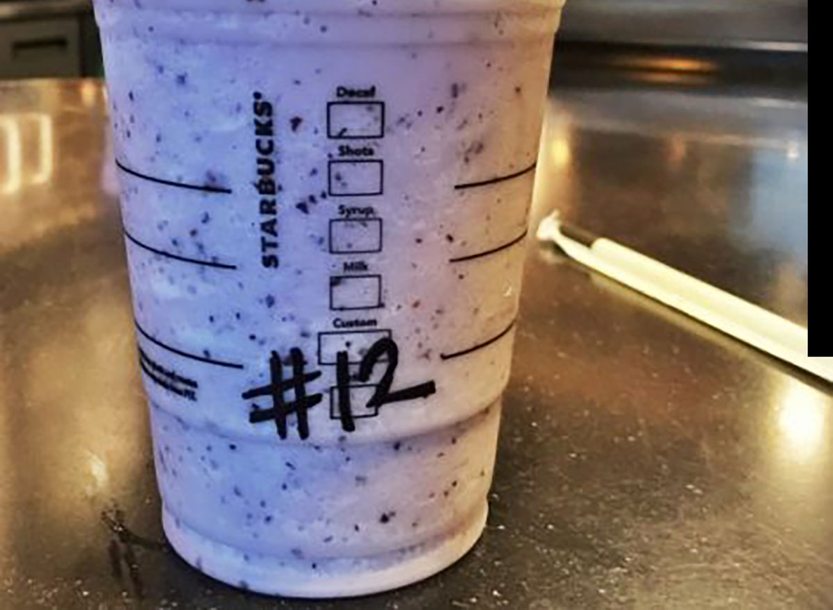 starbucks seahawks blueberry frappuccino with number 12 on table next to wrapped straw