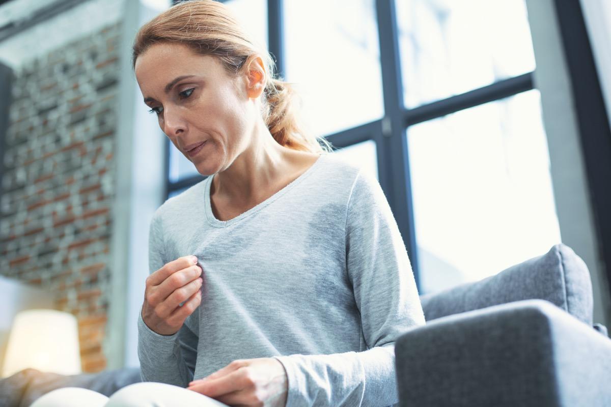 Sweating woman wearing sweater