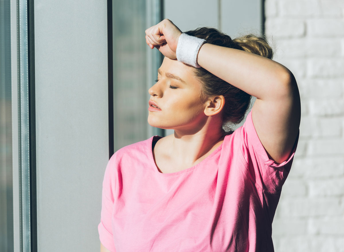 Tired woman exercising in pink shirt