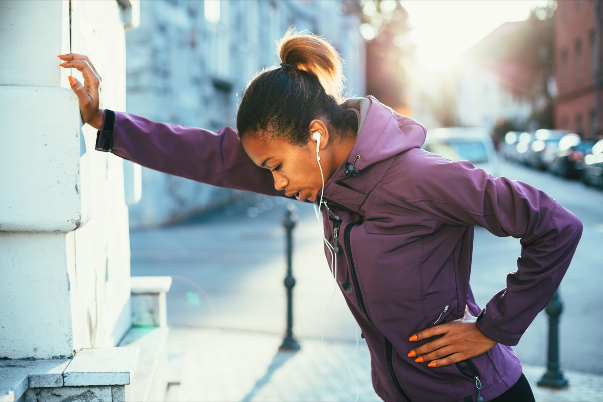 young woman stretching outside while running