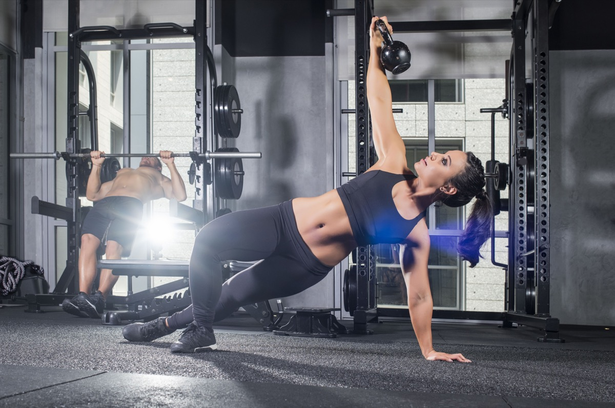 athletic female performs a Turkish get-up with a kettlebell wearing black sports outfit showing her abs