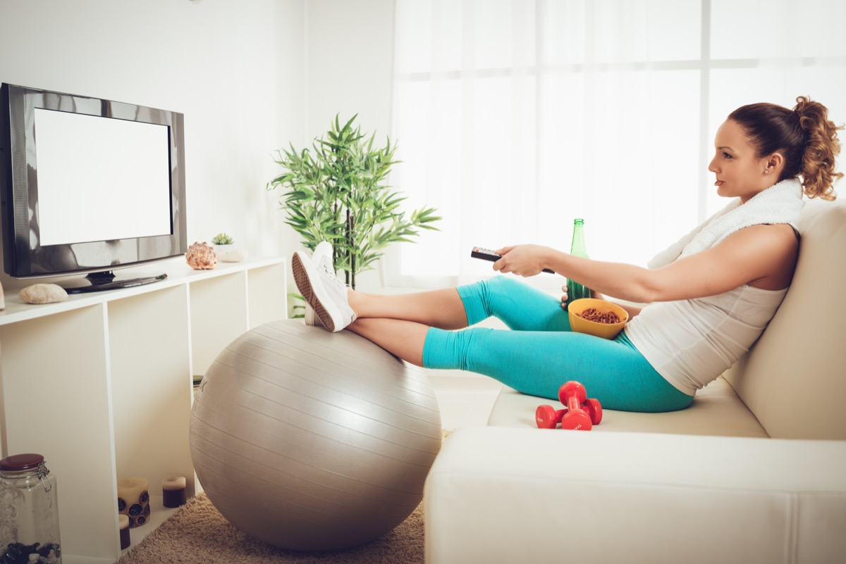 young woman in sport clothing sitting front of the TV and doesn't wont to exercise