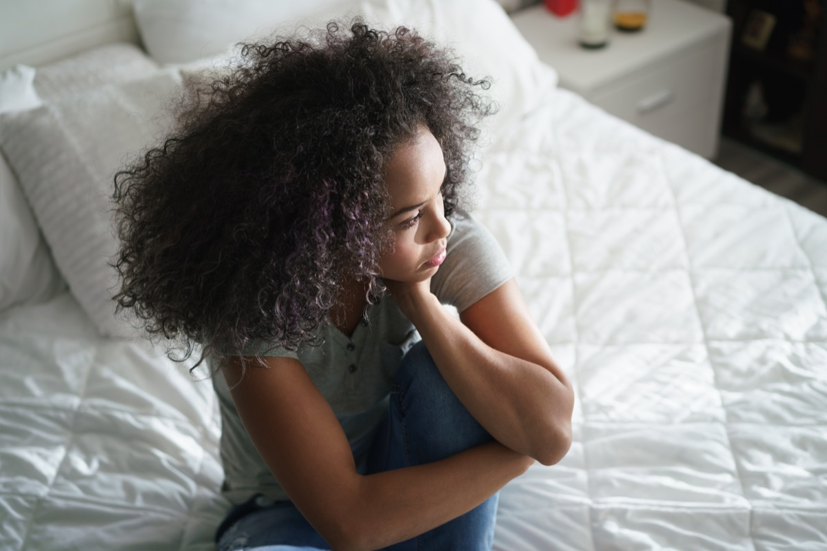 Lonely young latina woman sitting on bed. Depressed hispanic girl at home, looking away with sad expression