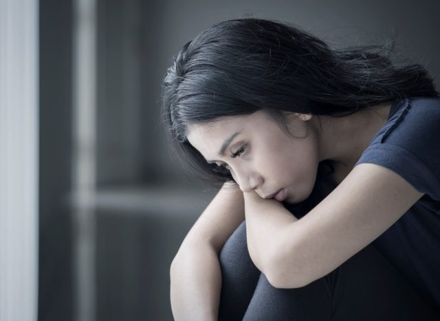 sad woman suffering anorexia while sitting in the black background