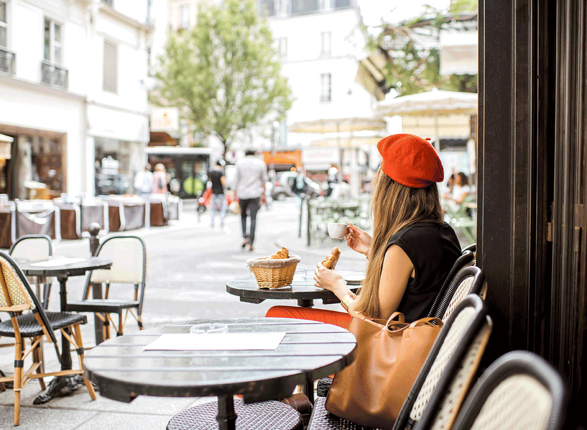 young woman red beret eating french breakfast coffee croissant outdoors at cafe table