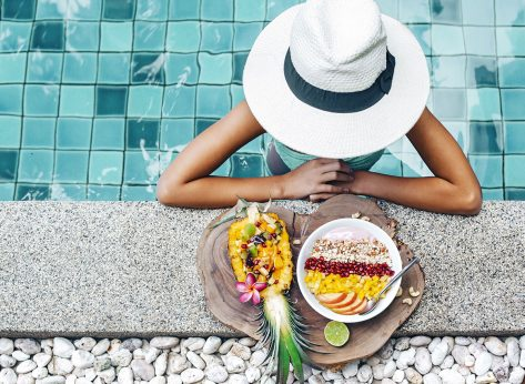 woman poolside at resort with smoothie bowl fresh fruit