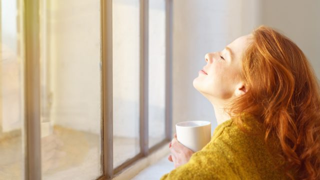 happy woman sitting by the window