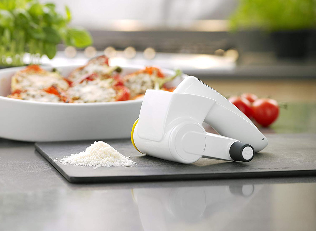 zyliss cheese grater with parmesan on black cutting board and stuffed peppers