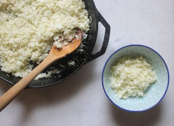 cauliflower rice in a skillet scooped into a blue bowl on a marble counter