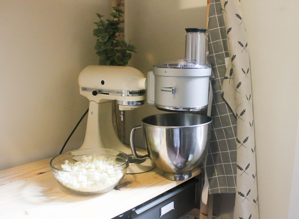 Kitchen Aid food processor on a counter with cauliflower ready to rice