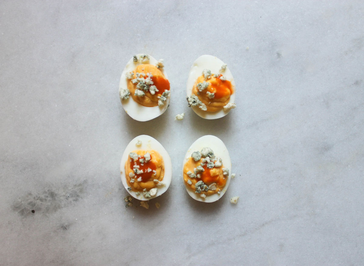 buffalo blue cheese deviled eggs on a marble counter