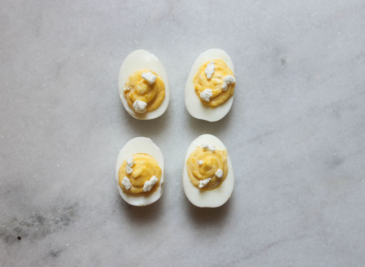 goat cheese deviled eggs on a marble counter