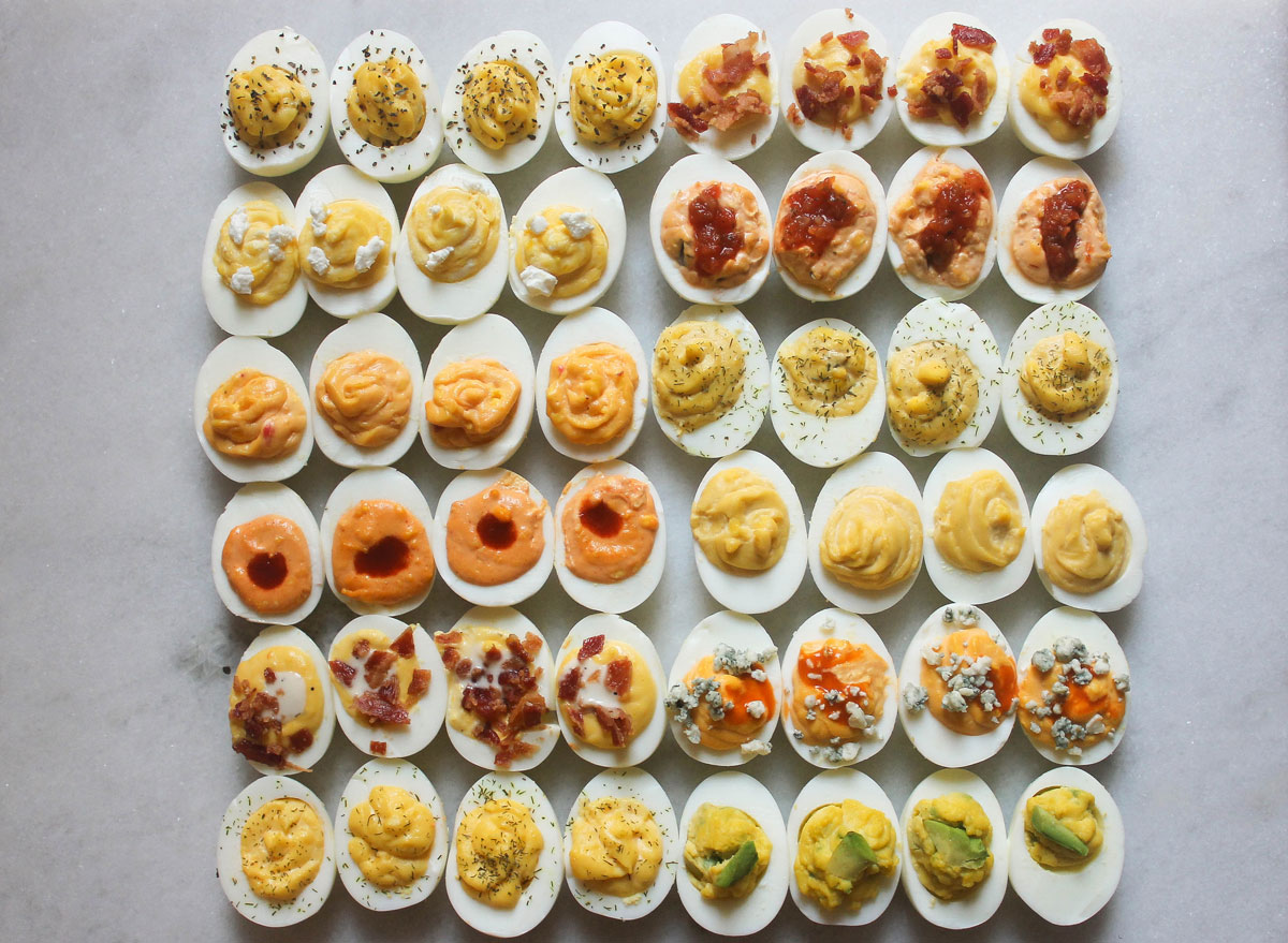 numerous deviled egg combinations all on a marble counter