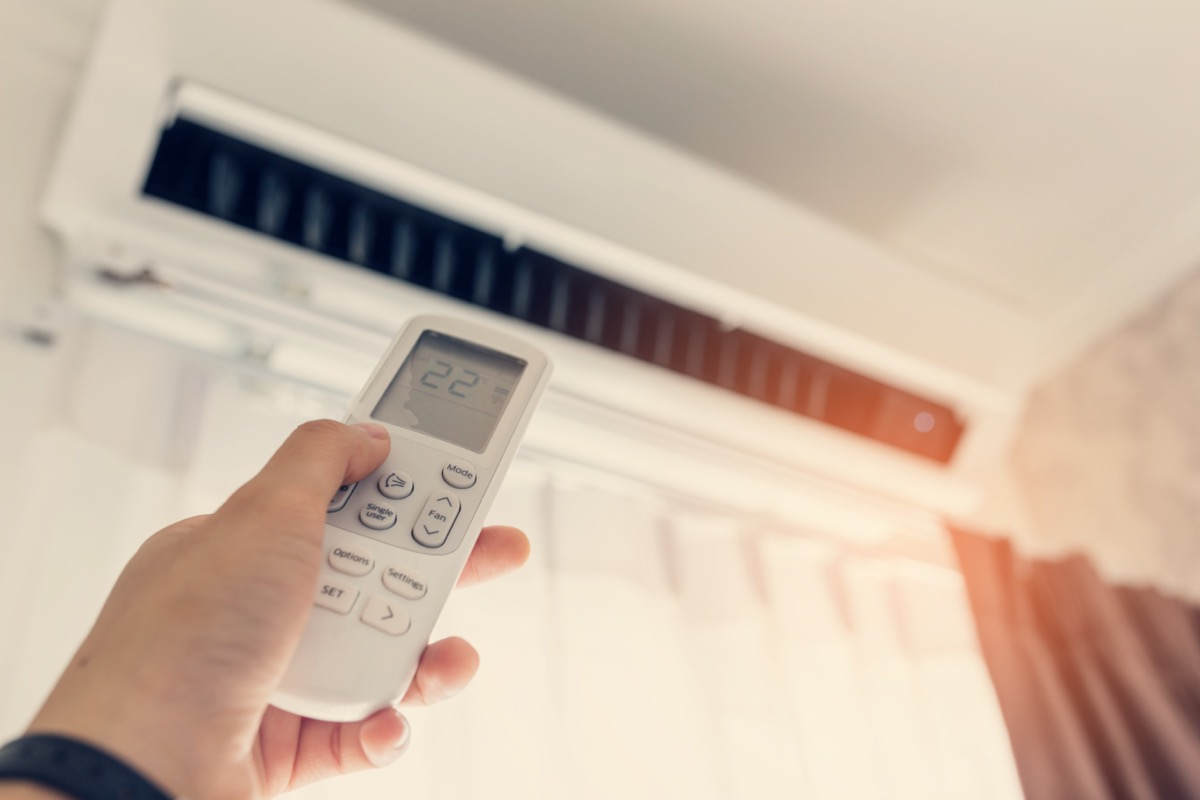 Air conditioner inside the room with woman operating remote controller