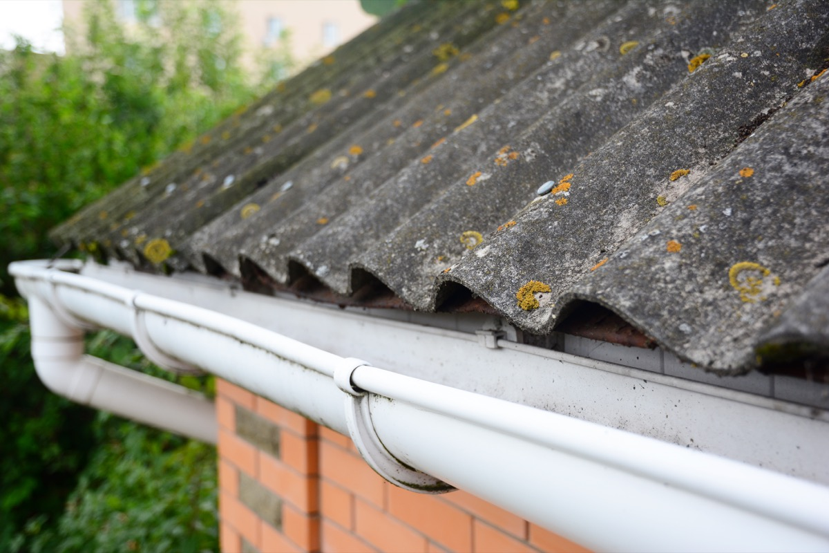 House asbestos roof with close up gutter holder and plastic roof gutter pipe.