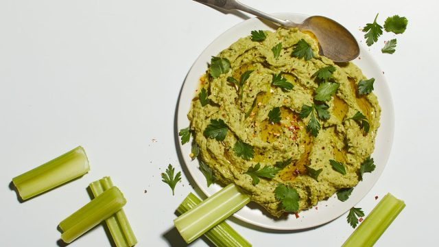 bowl of avocado hummus with celery and spoon