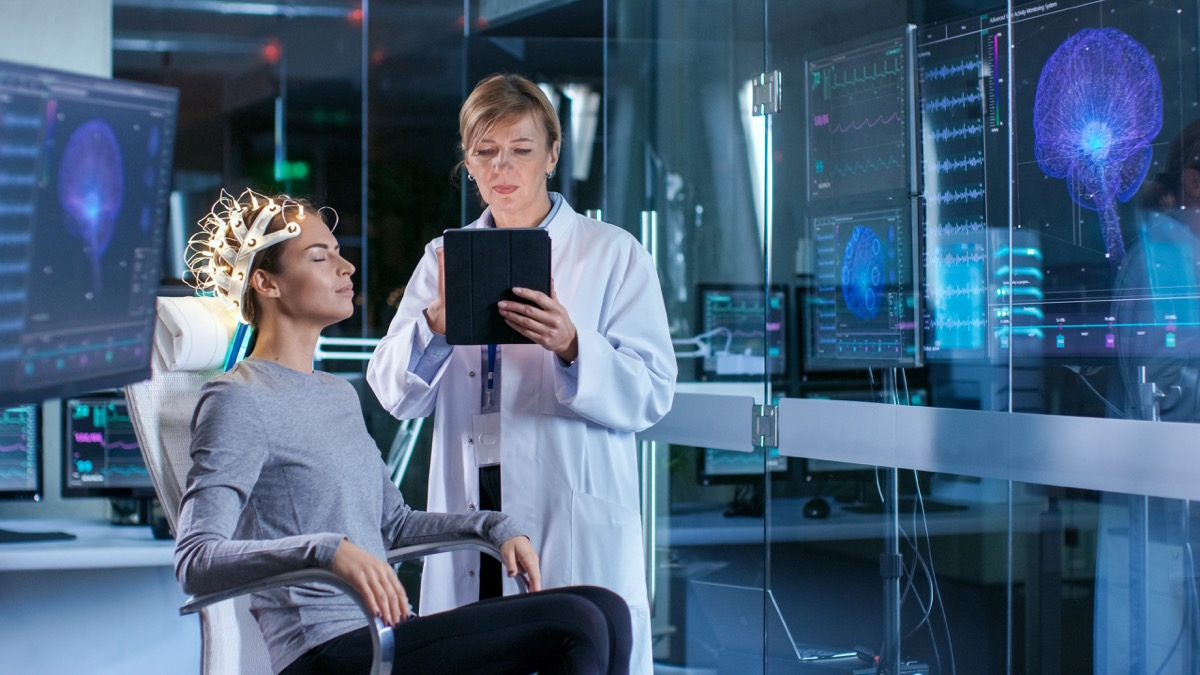 Woman Wearing Brainwave Scanning Headset Sits in a Chair while Scientist Adjusts the Device, Uses Tablet Computer. In the Modern Brain Study Laboratory Monitors Show EEG Reading and Brain Model. - Image