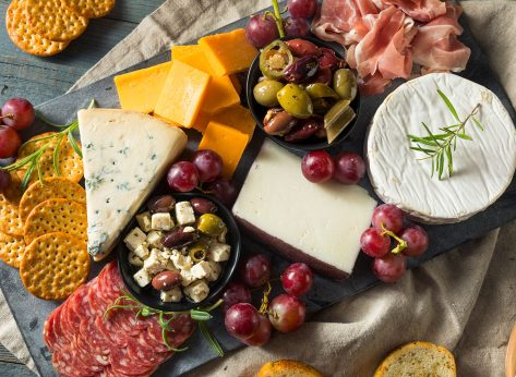charcuterie board with cheeses meats fruits and other toppings