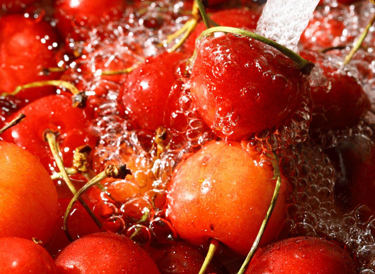 cherries being rinsed in a sink