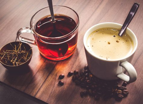 two mugs with coffee tea beans stems on wooden surface