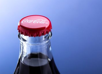 closeup on top of coke bottle with red cap
