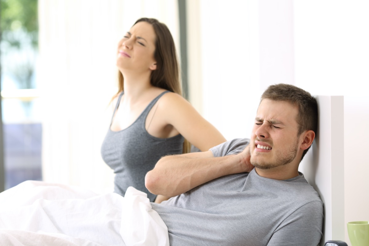 Couple waking up suffering ache after a bad night in a not comfortable bed at home.