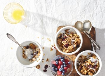 cranberry orange granola bowls with bowl of berries and spoons